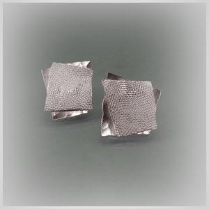 Ohrstecker aus zwei leicht gegen einander versetzten, unterschiedlich gehämmerten Silberplatten.
