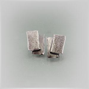 Ohrstecker in geschwärztem Silber. Mit jeweils zwei gekanteten, rechteckigen Flächen. Diese sind, unterschiedlich stark mattiert, leicht  versetzt zueinander verbunden.