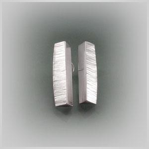 Ohrstecker in Silber mit längs gebautem, dreieckigem Körper. Die etwas breiteren Flächen tragen eine Querstruktur, die übrigen Flächen sind poliert.