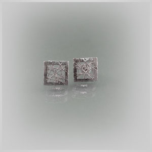Ohrstecker in Silber. Ungeordnet verlaufende Silberfäden liegen an einem quadratischen Rahmen.