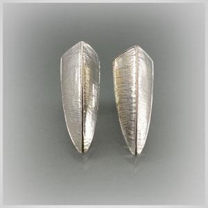 Ohrstecker in Silber, der dreieckige Körper trägt auf den Seitenflächen eine querlaufende Struktur. Rück- und Oberseite sind poliert.