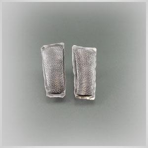 Ohrstecker in geschwärztem Silber. Eine fast rechteckige Form ist auf einer leicht größeren Platte angebracht, jeweils mit unterschiedlicher Oberfläche.