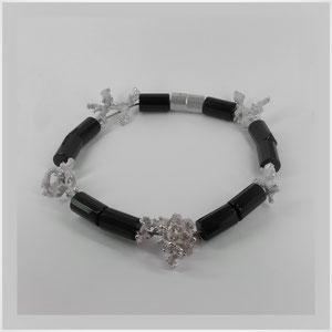 Collier mit organischen Zwischenteilen aus Silber, die mit einer speziellen Oberfläche aus unendlich vielen Kügelchen versehen sind, und welchen aus schwarzem Glas.