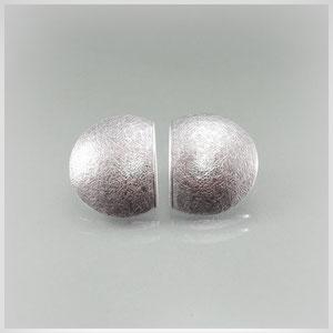 Ohrstecker in Silber mit schraffierter, leicht gewölbter Oberfläche und gerader Rückseite. Diese sind, ebenso wie die Seitenabschnitte, poliert.