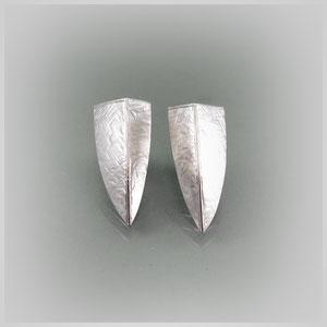 Dreieckig gearbeitete Ohrstecker in Silber, die Seitenteile zeigen eine gehämmerte Struktur, Rück- und Oberseite sind poliert.