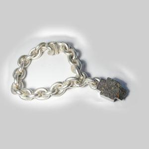 Schweres Armband in Silber. Die Kettenglieder sind mattiert, mit einem großen,kreuzförmigen Anhänger aus Stahl.