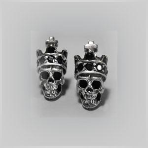 Ohrtecker mit kleinen gekrönten Totenköpfen. In Silber mit Onyx.