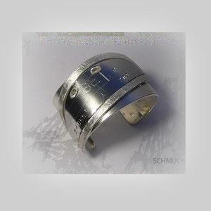 Armreif aus Silber. In der schraffierten Oberfläche ist ein individuelles Amulett aus Stahl eingefasst.