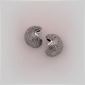 Ohrstecker in Silber. Zwei aufeinander liegende Halbschalen wirken durch die dunkel gewundene  Gravur.