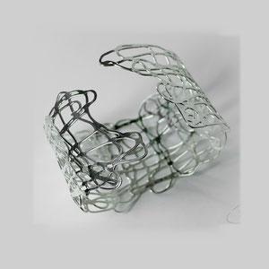 Armreif in Silber mit durchbrochener, organisch anmutender Struktur.