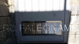 Griglia di Areazione in Acciaio Inox fissata sulla Porta in Ferro