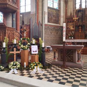 Aufbahrungsdekoration zum Requiem in einer römisch-katholischen Kirche vor der Urnenbeisetzung mit Leuchtersäulen, Rispengräsern und Holzsäulen ohne Hintergrundbanner