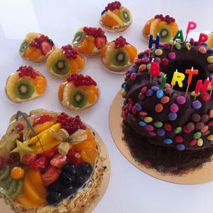 Schokomarmorguglehupf (rechts) mit Smarties - der beliebteste Kuchen für Kindergeburtstage. Ergänzt durch einen Mehrfruchtkuchen (links) sowie Mini-Frucht-Tartelettes