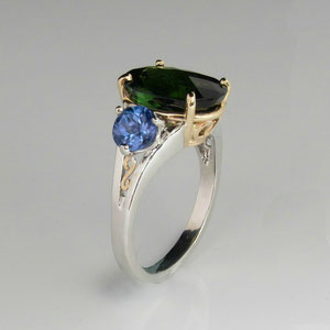 CS 4 - 14K two toned gold  ring with center oval peridot side tanzanites, and decorative scrolls.