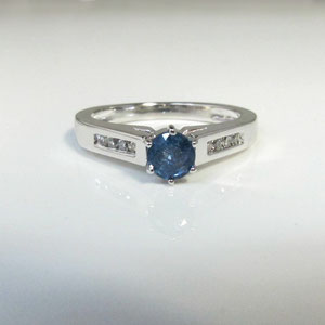 CS 29 - 14K white gold ring with center sapphire and channel set diamonds.