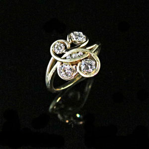 DF 4 - 14k yellow and white gold swirl ring features 4 prong set diamonds accented with 3 channel set diamonds.