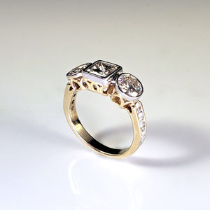 WF 51 - 14K three stone ring with center princess cut diamond, two round side diamonds. and channel set melee diamonds.