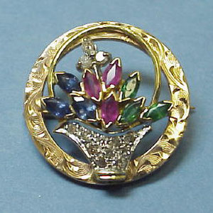 PB 14 - 14k yellow and white gold pin with a multi stone floral arrangment and diamond basket.