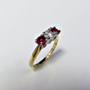 DF 36 - Platinum and 14K yellow gold 3 stone ring with center diamond and side rubies.