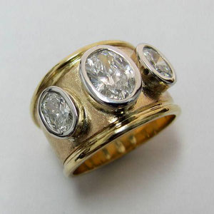WF 14 - 14K two toned gold wide band with three bezel set oval diamonds.