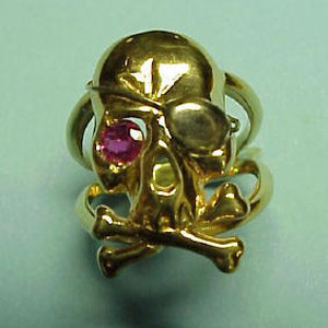 G 4 - 14K yellow gold scull complete with patch and a ruby eye.