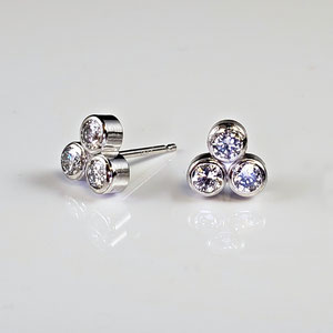 E 116 - 14K white gold earrings with bezel set diamonds.