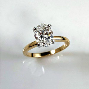 WF 46 - 14K two tone solitaire engagement ring with oval diamond.