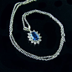 P 47 - 14k white gold Princess Di style sapphire and diamond pendant.