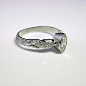 WF 24 - Paladium ring with bezel set marquiese diamond. Hand carved embeleshments.