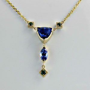 P 5 - 14K yellow gold lavalier with tanzanite, and emeralds.