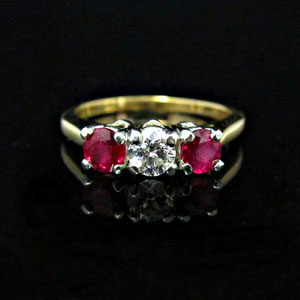 CS 39 - Platinum and 14K yellow gold 3 stone ring with center diamond and two rubies.