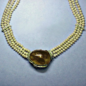 P 29 - 14K green gold necklace with amber and peach colored pearls.