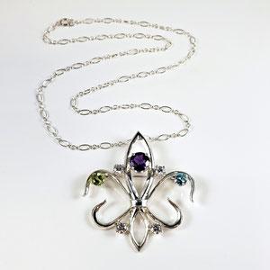 P 128 - Fleur de lis pendant with zircon, amethyst, and peridot.