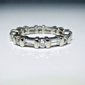 B 21 - Platinum band with bar set round and baguette diamonds.