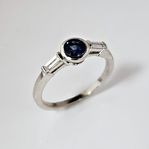 CS 49 - 14K white gold ring with center bezel set sapphire and two baguette diamonds.