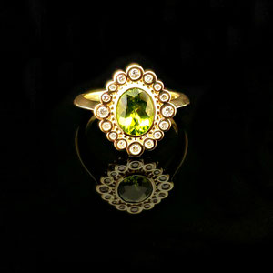 CS 43 - 14K yellow gold ring with bezel set center peridot surrounded by diamonds.