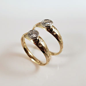 B 29 - 14K two tone custom wedding bands with bezel set diamonds.