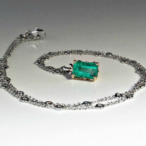 P 16 -  14K yellow gold pendant with emerald cut emerald.  14K white gold chain.