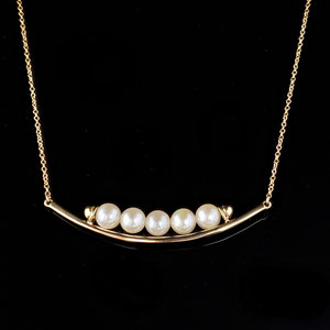 P 85 - 14K yellow gold 'smile' necklace with pearls.