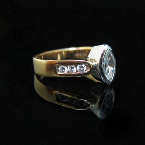 AN 16 - 14K two toned ring with bezel set marquise center diamond and channel set diamonds.