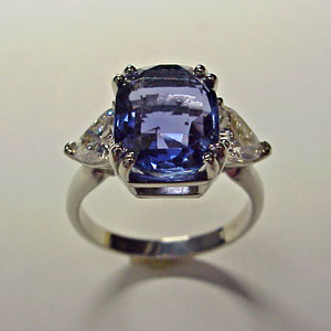 CS 25 - 14k white gold ring featuring a center tanzanite and trillion side diamonds.