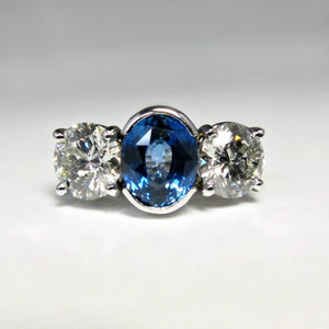 CS 37 - 14K two tone ring with oval sapphire set in a semi bezel, and two side diamonds.