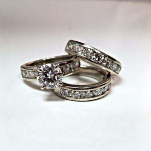 WF36 - Platinum wedding set with center diamond and channel set diamonds.