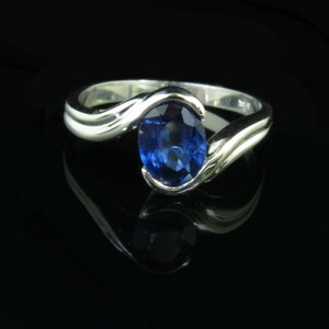 CS 26 - 14k white gold bypass ring with an oval sapphire focal stone.