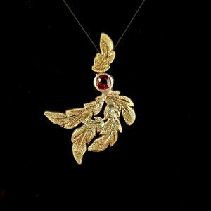 P 130 - 14K yellow gold 'feather' pendant with bezel set garnet.