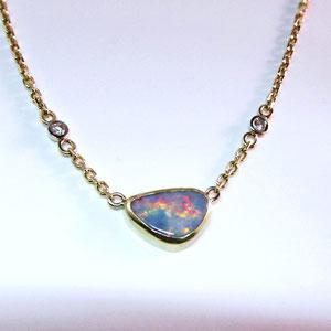 P56 - 14K yellow gold bezel set opal pendant with diamonds.