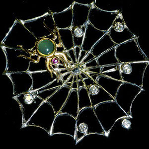 PB 10 - 14K white gold spider and web with cabochon emerald, diamonds, and a ruby.