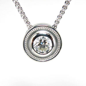 P 61 - 14K white gold bezel set diamond pendant.