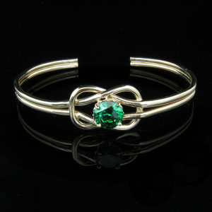BR 1 - 14K yellow gold cuff bracelet with a hand fabricated knot surrounding a green tourmaline.