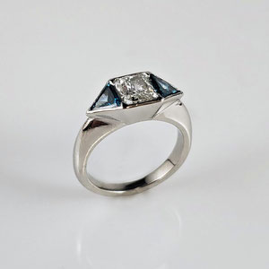 DF 50 - Platinum ring with blue trillion diamonds and center emerald cut diamond.